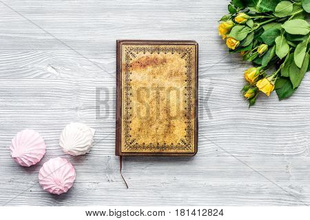 spring flatlay with flowers, notebook and marsh-mallow on light wooden work desk background top view mock up