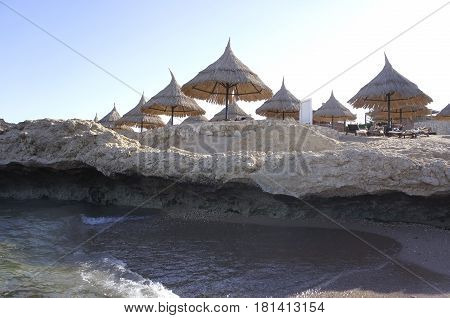 Coral coast and beach umbrellas. Beautiful landscape