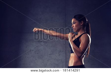 sport, fitness, martial arts and people concept - woman boxing and making punch in gym