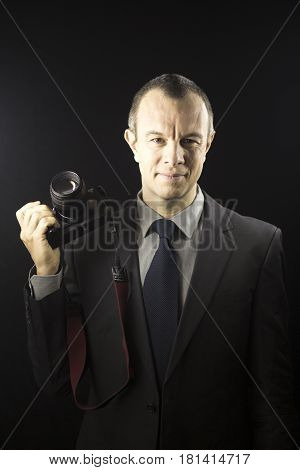 Photographer in studio in suit with camera aged in 40's against plain studio portrait background.