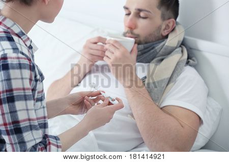 Young woman taking care of ill man sitting in bed at home