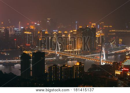 Chongqing China - Dec 22 2015: The night view of foggy crowded city beside the jialing river