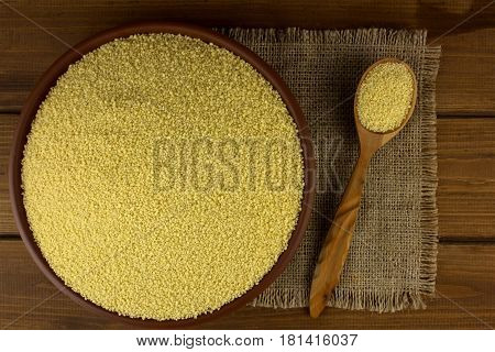 Couscous into a bowl on the table and wooden spoon