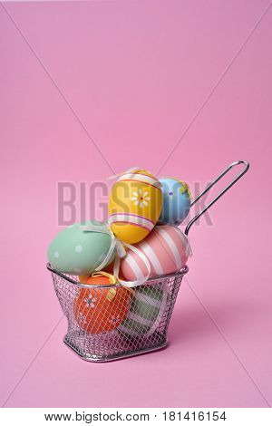 a pile of different decorated easter eggs in a metal basket against a pink background with a blank space on top