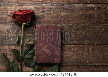 a red rose and an old book on a rustic wooden table, with a blank space, for Sant Jordi, the Catalan name for Saint Georges Day, when it is tradition to give red roses and books in Catalonia, Spain