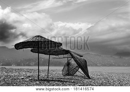 Black And White Old Sunshade On Deserted Beach
