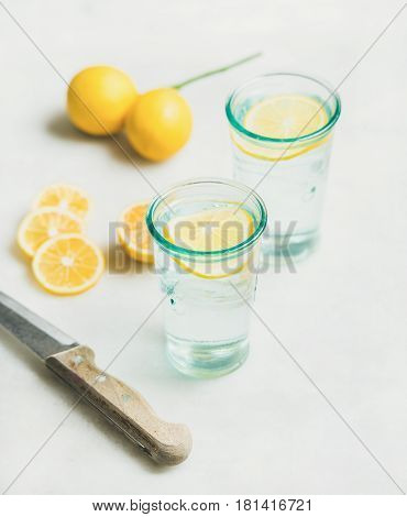 Morning detox lemon water in glasses and fresh lemons over marble background, selective focus. Clean eating, weight loss, healthy, detox, dieting concept