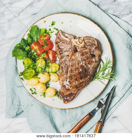 Grilled meat dinner plate. Cooked beef tbone steak with vegetables and fresh rosemary over marble table background, top view, square crop
