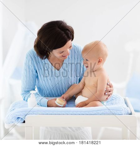 Mother Changing Diaper To Baby Boy