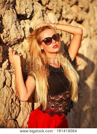 Sensual woman enjoys the hot sunlight by the stone wall