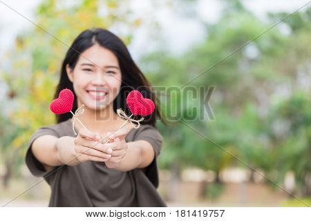 giving love in valentine's day Asian woman hand hold give beautiful red heart sweet loving symbol of take care or charity help to you.
