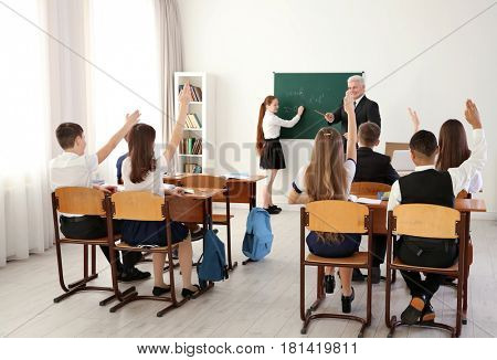 Pupils raising hands to answer at lesson in classroom
