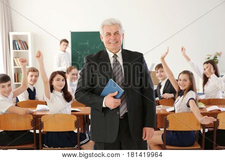 Senior teacher with notebook and happy pupils on background