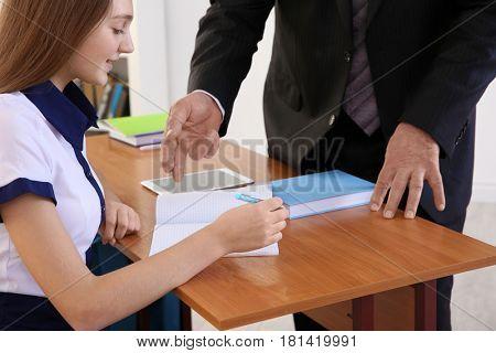 Senior teacher explaining exercise to schoolgirl in classroom