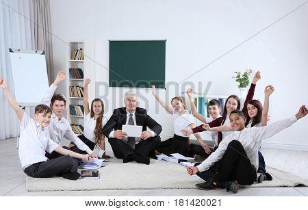 Happy pupils and senior teacher sitting on floor in classroom