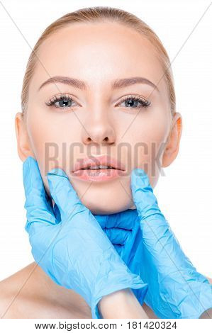 Cosmetologist Examining Chin Of Patient
