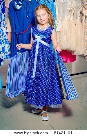 Pretty little girl child with shopping bags in the store of children's clothes. Seasonal sale and shopping. Kid's fashion.