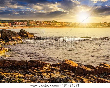 SOZOPOL BULGARIA - SEPTEMBER 11 2013: rocky shore and sandy city beach in mellow season. Beautiful and warm weather on the coast of Black sea at sunset.