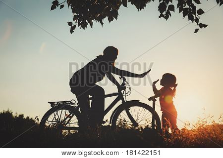 mother and little daughter riding bike and scooter in sunset nature