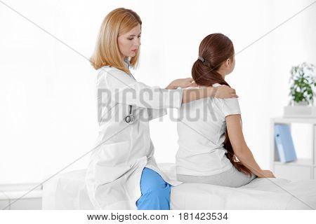 Incorrect posture concept. Physiotherapist examining and correcting girl's back