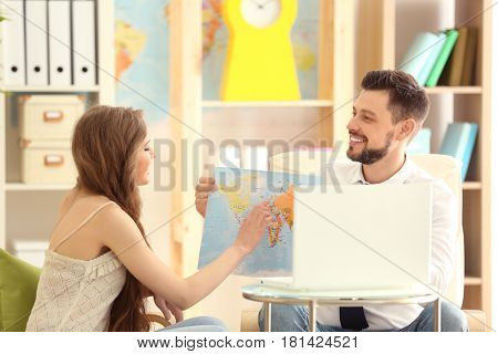 Adventure concept. Young woman discussing future trip with travel agent in office