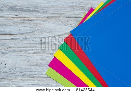 Sheets of color paper on wooden background rainbow corner