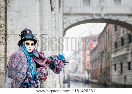 Blue masked carnival costume with hat catching a ride next to famous Bridge of Sighs, Venice,Italy.