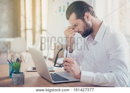 Overworked Young Man Having Headache After Hard Working Day And Touching His Face