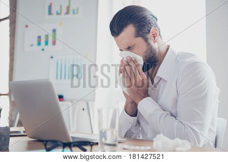 Sick Businessman With Temperature Works In Office And Wipes His Nose With A Napkin
