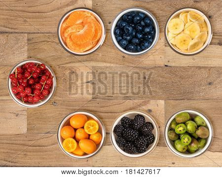 Top view of a white glass bowls of various sorts of organic fruits including, banana, orange, blueberry, redcurrant, kumquat, blackberry and kiwi berry and sitting on old wood table surface