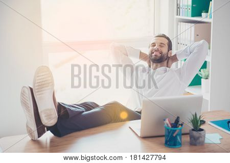 Handsome Young Dreamy Man Is Sitting In The Workplace Putting His Feet On The Table In Lightful Offi