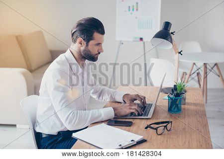 Side View Of Confident Bearded Concentrated Businessman In White Shirt Works On Laptop While Sitting