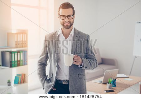 Happy Handsome Businessman In White Shirt And Jacket Holds Mug Of Drink In Office While Taking Hand