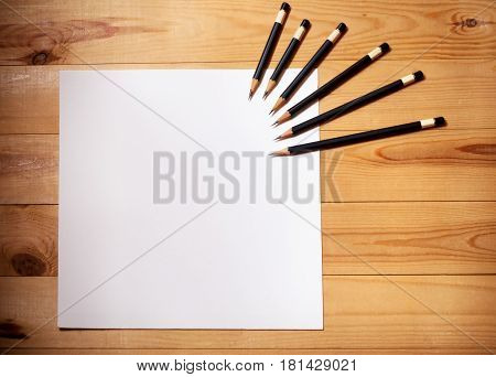 Blank paper and pencils on wooden background. View from above