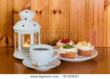 Cup of coffee sweet cakes with fruits and lantern on wooden table