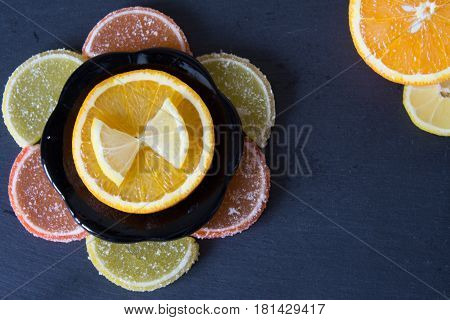 Colorful sugary marmalade like lemon and orange slices covered with sugar. Fruit jelly candies.Closeup. Top view on slate.
