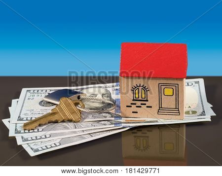 Toy wooden home on US 100 dollar bills with a door key and lock to illustrate house purchase or rental. Mortgage payments to a bank are implied.