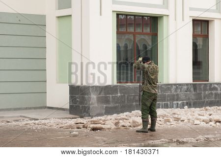 A Man Clears The Sidewalk Of Ice, The Worker Of Municipal Services On The Street, Late Spring,