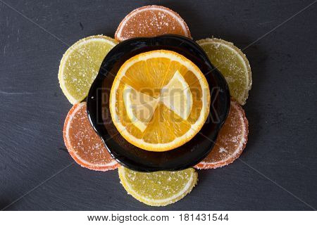 Colorful sugary marmalade like lemon and orange slices covered with sugar. Fruit jelly candies. Closeup. Top view on slate.