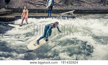 Munich-Germany - April 04, 2014: 15.Surfing in Munich at Englischer Garten is dangerous but possible: at one channel crossing the park a big artificial wave is generated on a concrete step