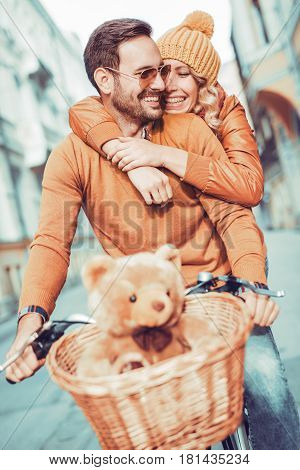 Couple in love in autumn.Happy young couple going for a bike ride on a autumn day in the city.
