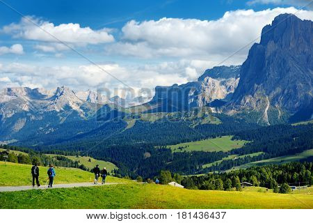 Tourists Hiking In Seiser Alm, The Largest High Altitude Alpine Meadow In Europe, Stunning Rocky Mou