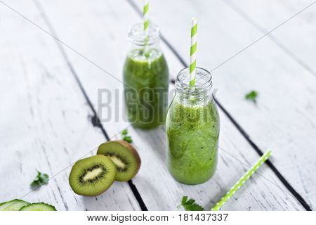 green smoothie, healthy, organic drinks with fresh vegetables and fruits. Two smoothie glasses with drinking straw on a white table. Close-up shot.