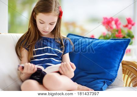 Adorable Little Girl Reading A Book In White Living Room On Beautiful Summer Day