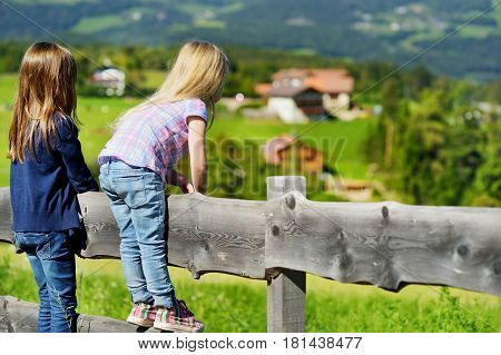 Two Little Sisters Admiring Beautiful Landscape In Dolomites Mountain Range, South Tyrol Province Of