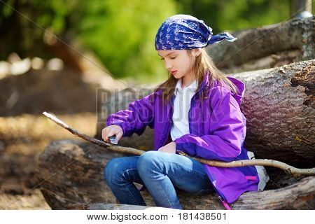 Cute Little Girl Sitting On Tree Logs Using A Pocket Knife To Whittle A Hiking Stick
