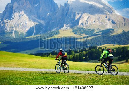 Tourists Cycling In Seiser Alm, The Largest High Altitude Alpine Meadow In Europe, Stunning Rocky Mo