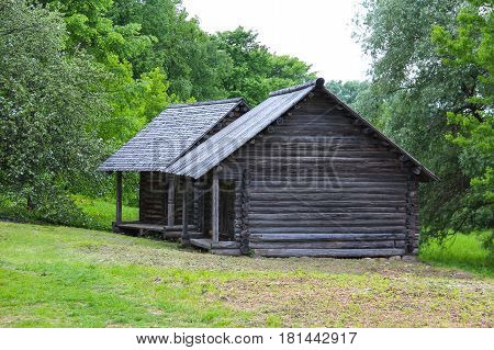The ancient wooden house in village on a green background
