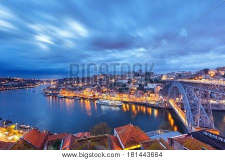 Picturesque panoramic aerial view of Old town of Porto, Ribeira and Dom Luis I or Luiz I iron bridge across Douro River during evening blue hour, Portugal