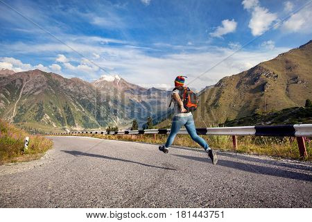 Tourist woman with backpack and rainbow hat running down the asphalt road in the mountains near Big Almaty Lake in Kazakhstan
